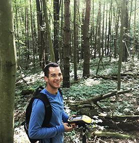 Kelson Perez '21 surveying plants in the Arboretum