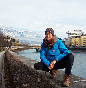 Student sitting on a stone wall in front of water with mountains in the background